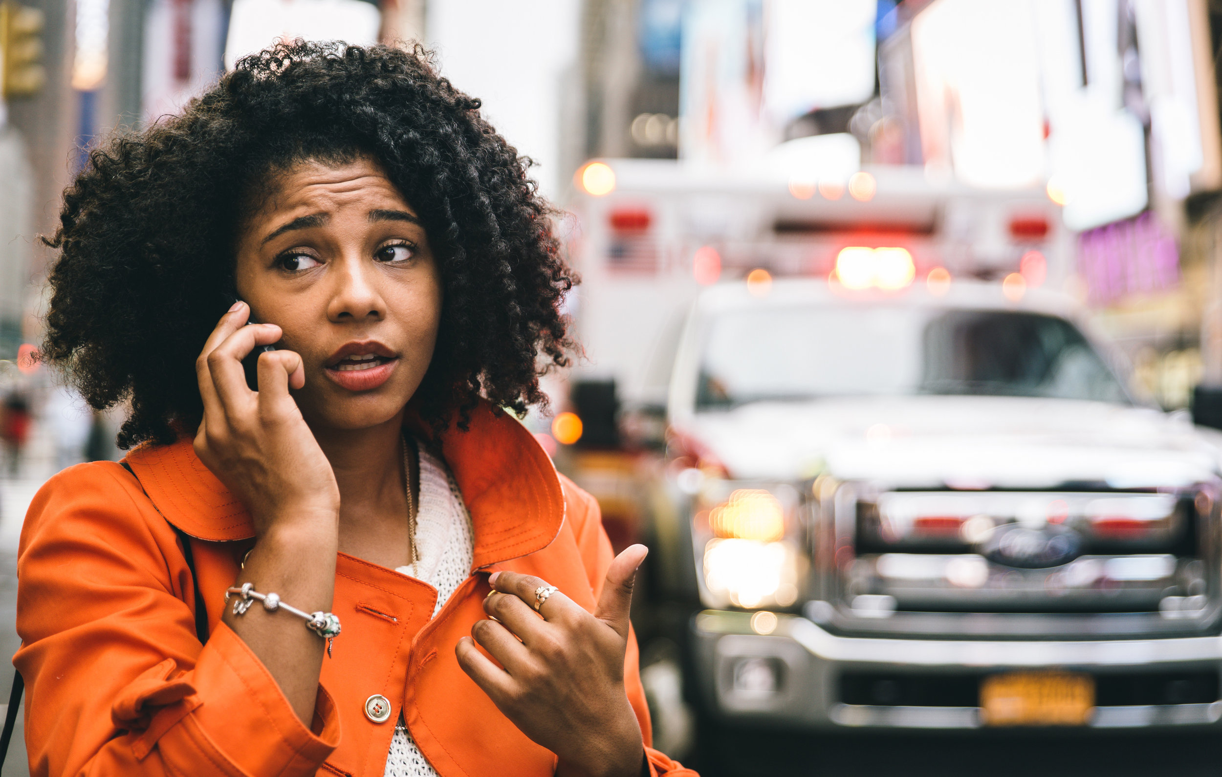 Woman on phone with ambulance in background
