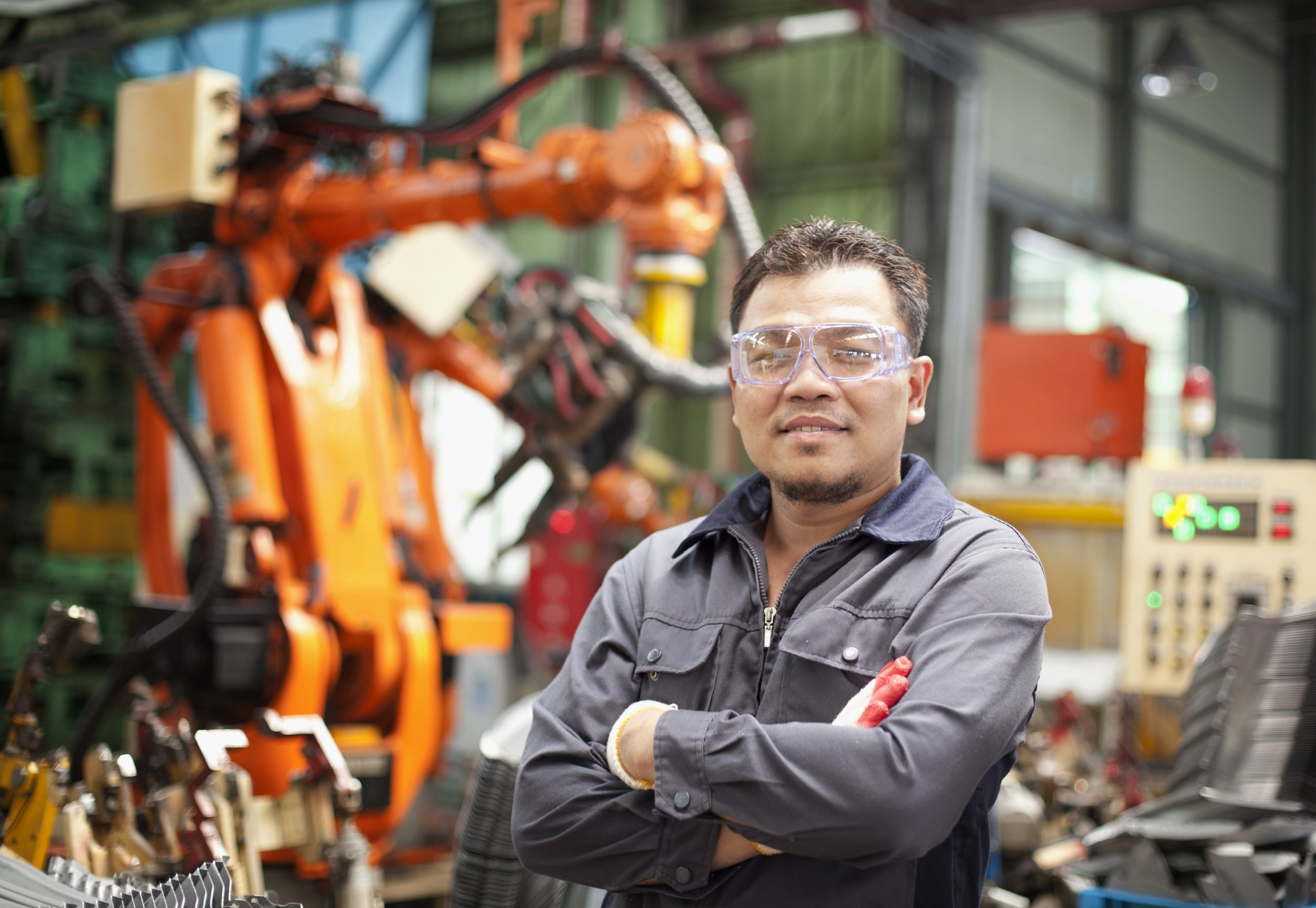 Machinery worker with robot in the background