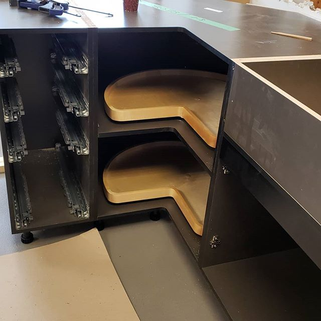 "Showroom. Install. Begins!! Check out how the gorgeous ""Slate"" sets off the wood accessories. Who needs Captain Marvel when you have Super Susans! #nopole .  Come down to the showroom and have a coffee or tea on us and watch the 2 (and a half) new displays come together before your eyes. . . #kitchensdesignedforlife #industrialloft #vancouvermillwork #vancouver #northvancouver #our40thyear @nickelscabinets #progresspic"