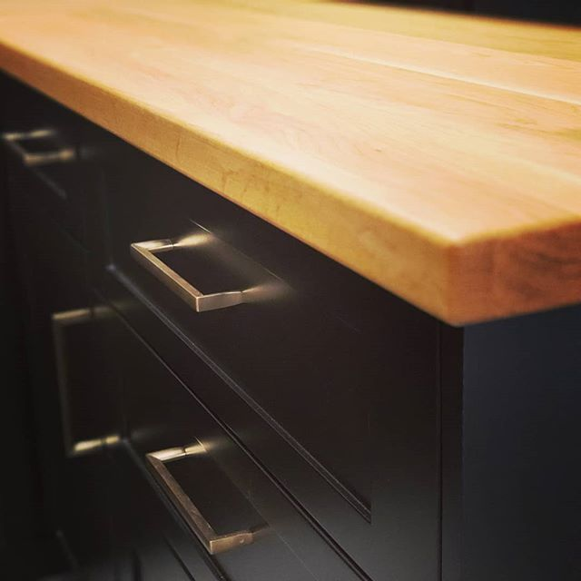 Black lacquered fronts, waterproof Caribou white oak counters, concrete floors, and gold handles. The newest addition to our showroom display collection. . Drop by the showroom for a look-see and a coffee. #kitchensdesignedforlife #custommillwork #kitchendesign #millwork #industrial