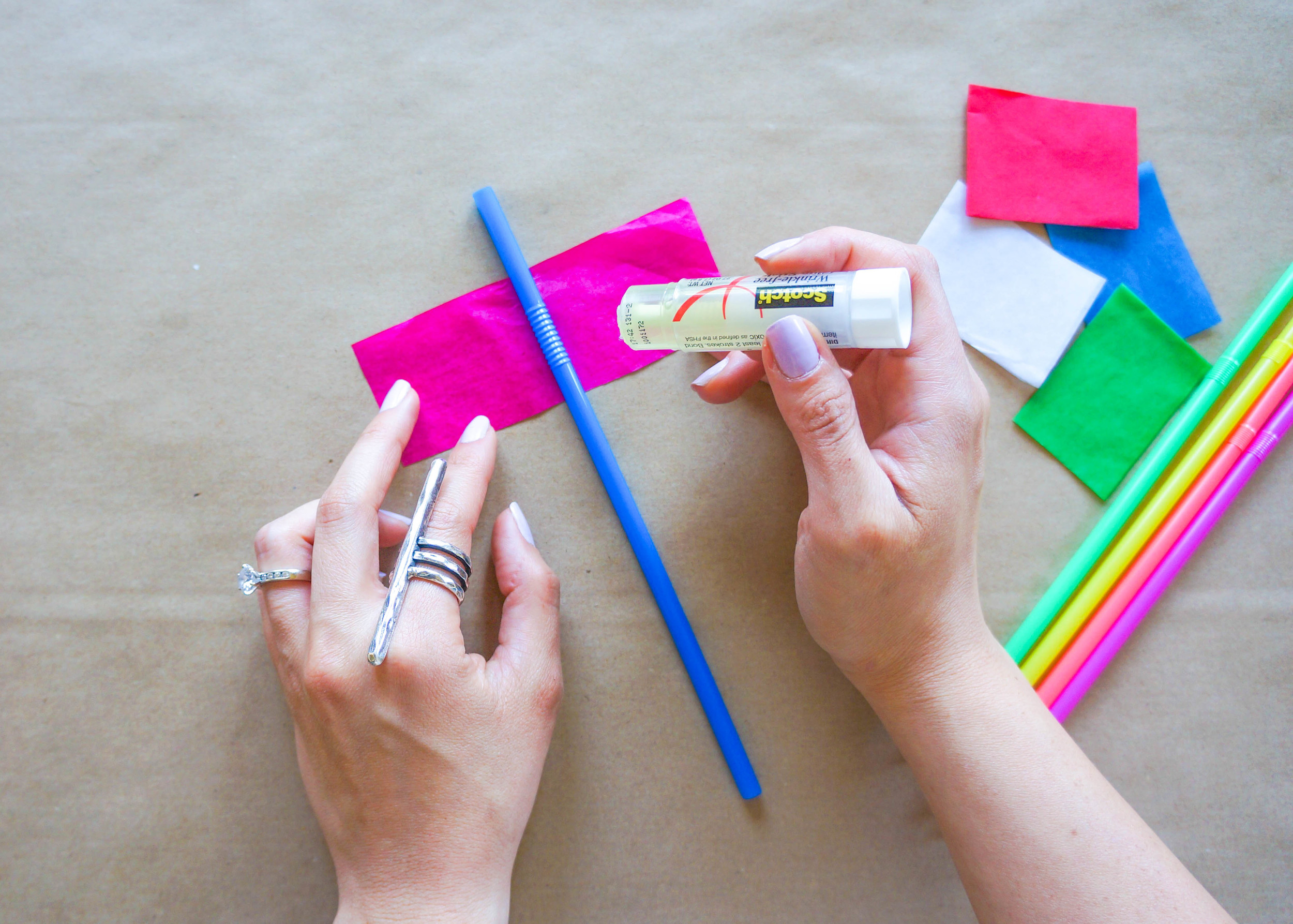 With your glue stick, apply an even layer of glue to one side of your tissue paper. Place your straw in the middle and fold the the paper in half, around the straw, lining up all corners and edges of the paper.