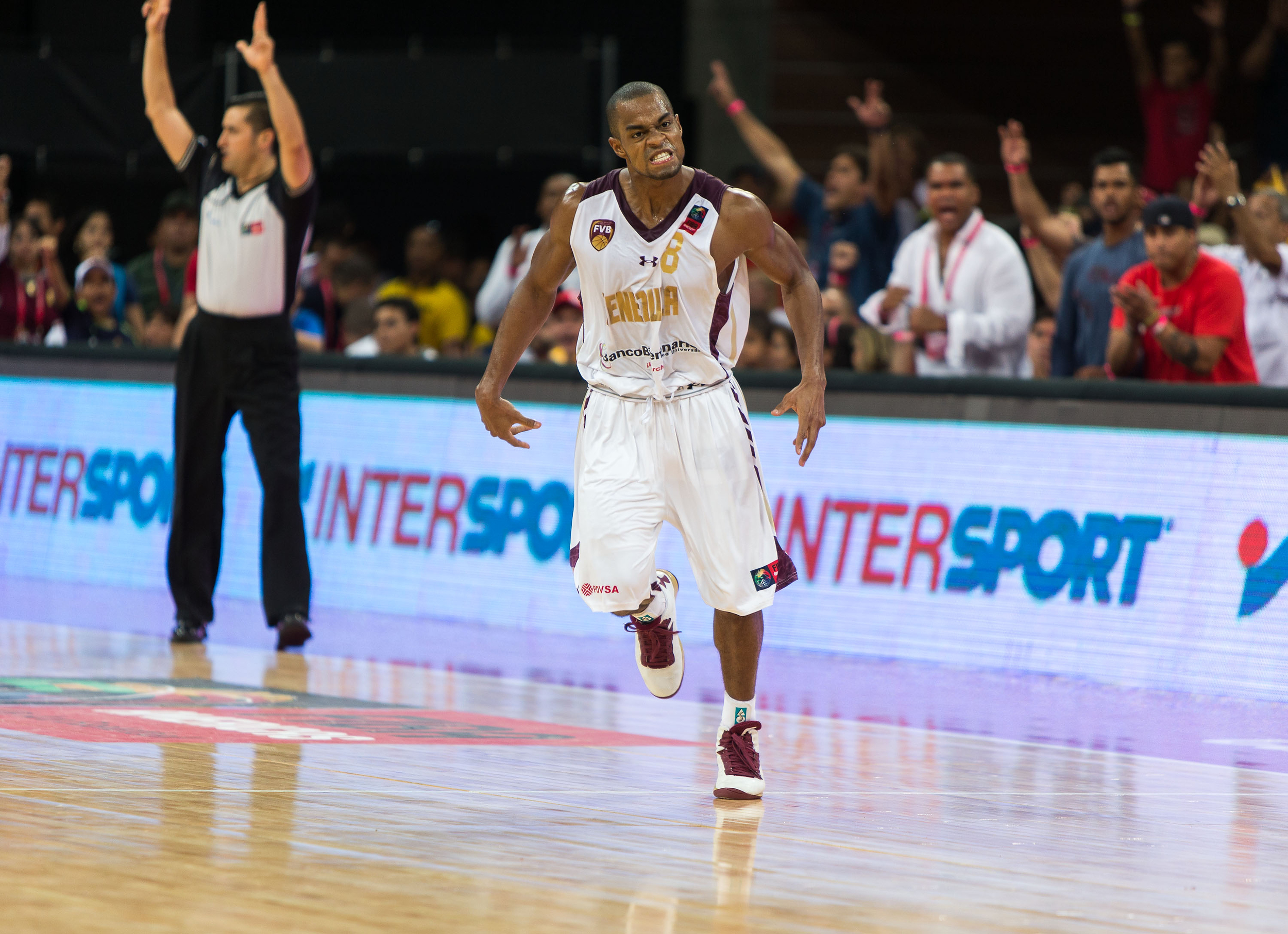 David Cubillan celebrates a three in the middle of a furious run by his Venezuela team, much to the delight of the rambunctious crowd.