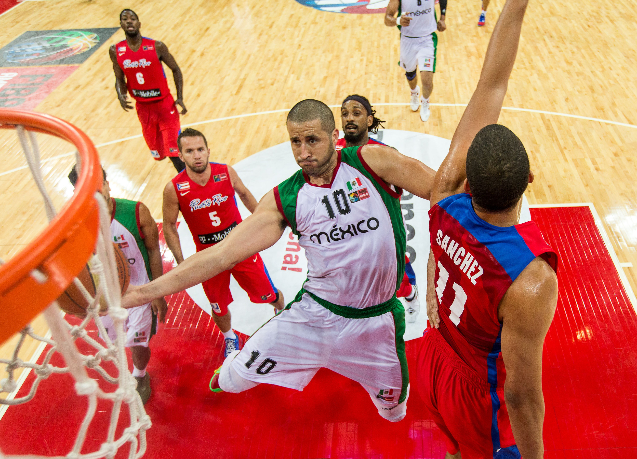 Mexico's Hector Hernandez extends past the defense of Puerto Rico's Ricardo Sanchez for an acrobatic finish in the FIBA Americas Championship games. Mexico went on to qualify for the 2014 World Cup in Spain and win the championship over Puerto Rico.