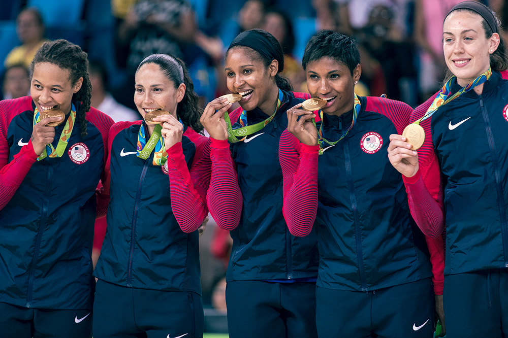 Team USA bites into their gold medals in Rio.