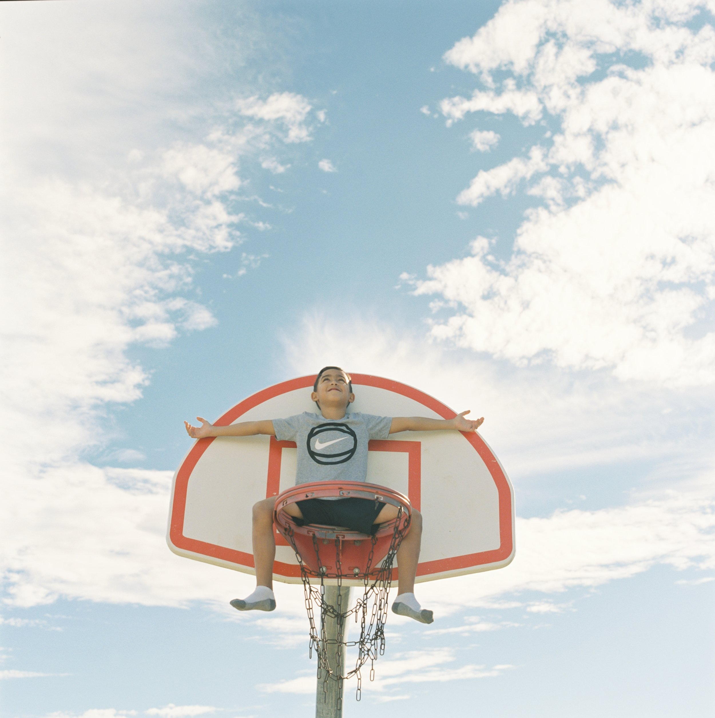 Sebastian sits on the basket in the sky. Dallas, TX 2017. Shot on a Hasselblad 501cm with Fuji Pro 400h film.