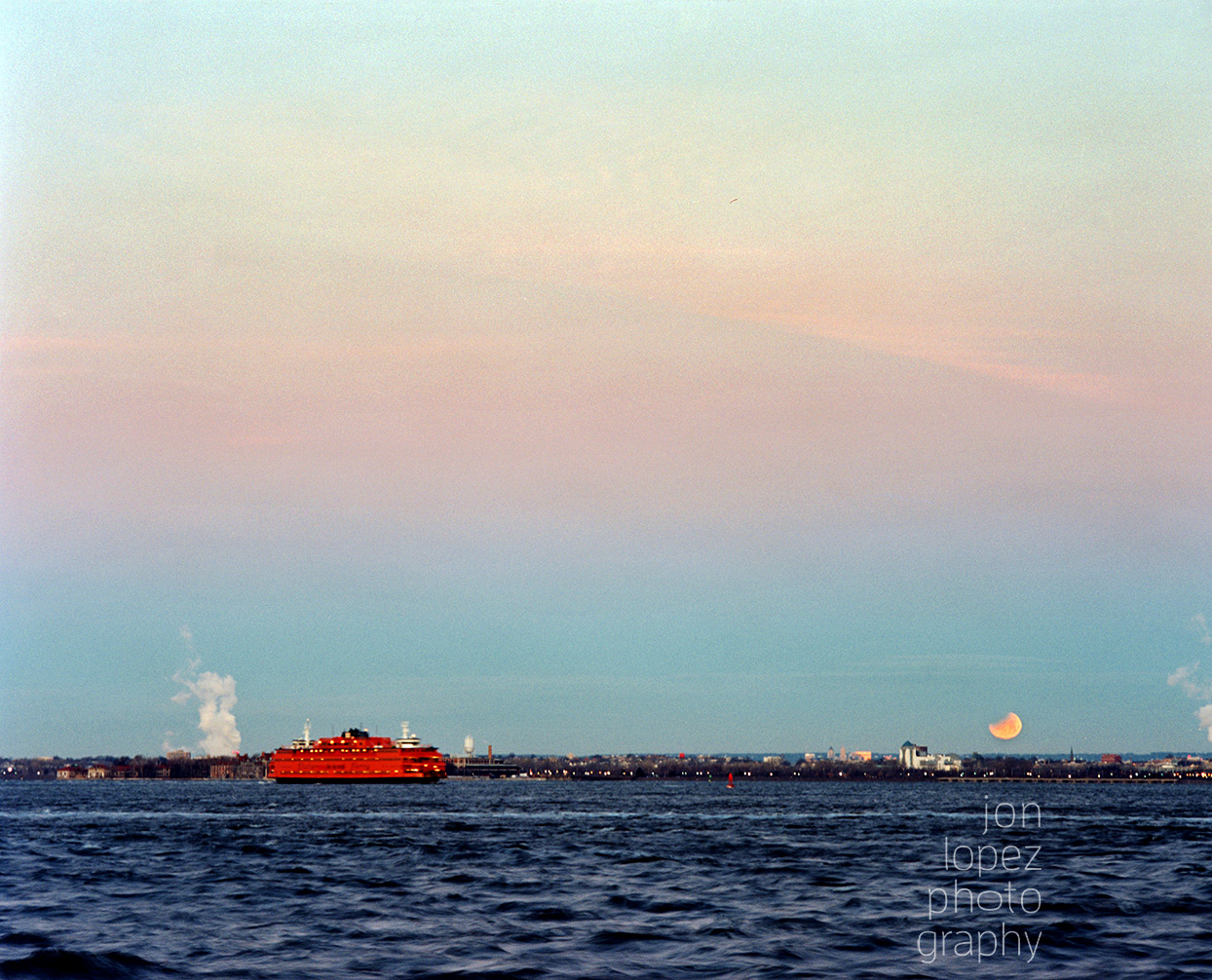 The Staten Island ferry heads to lower Manhattan as the super blue blood moon sets beyond the Hudson River. This image was shot on Fuji Pro 400h film using a Mamiya RB67 medium format camera. Photo credit: Jonathan Lopez