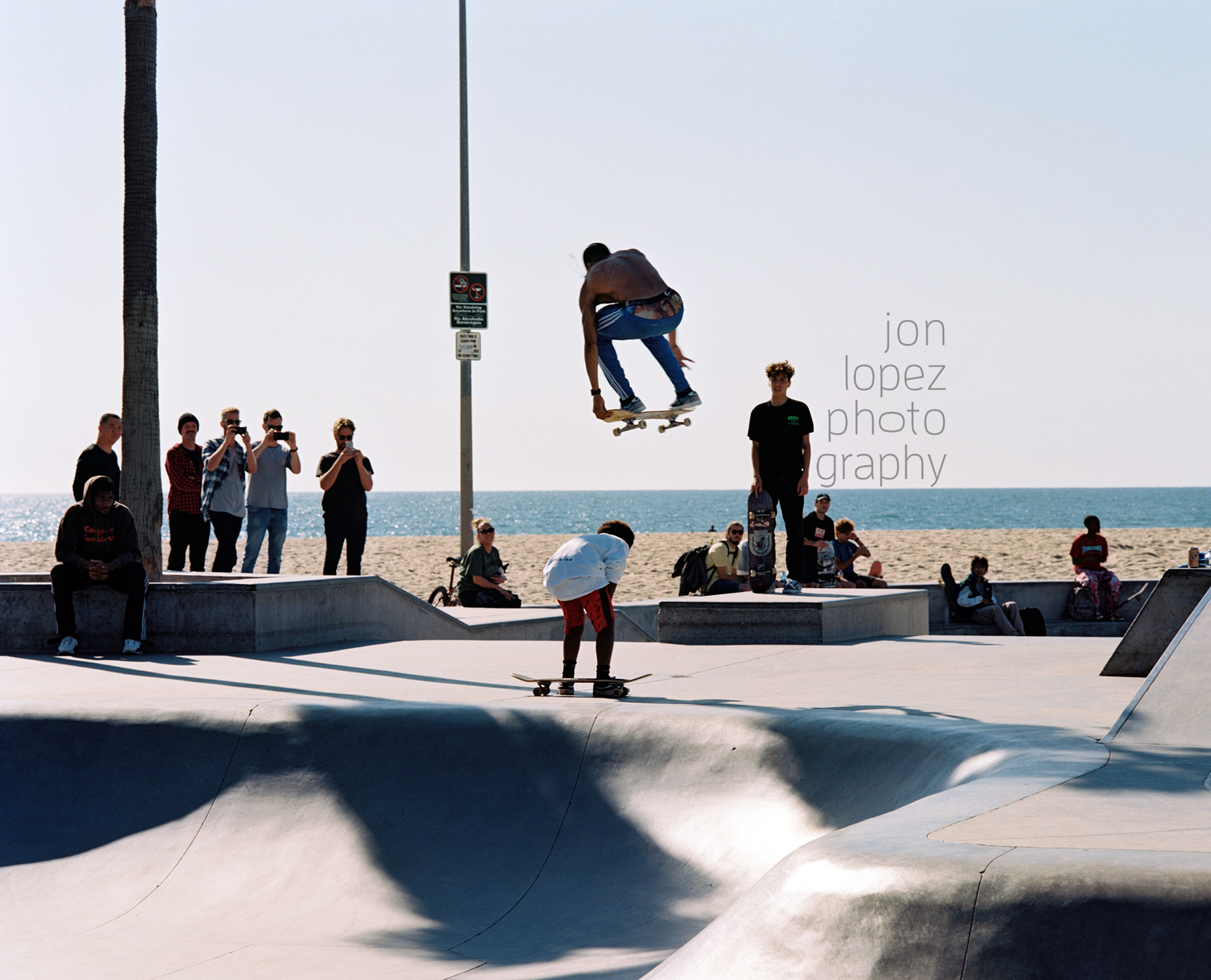 Venice Beach regular skater Isaiah Hilton takes to the sky over a young man much to the delight of the crowd. Shot on Kodak Portra 400.