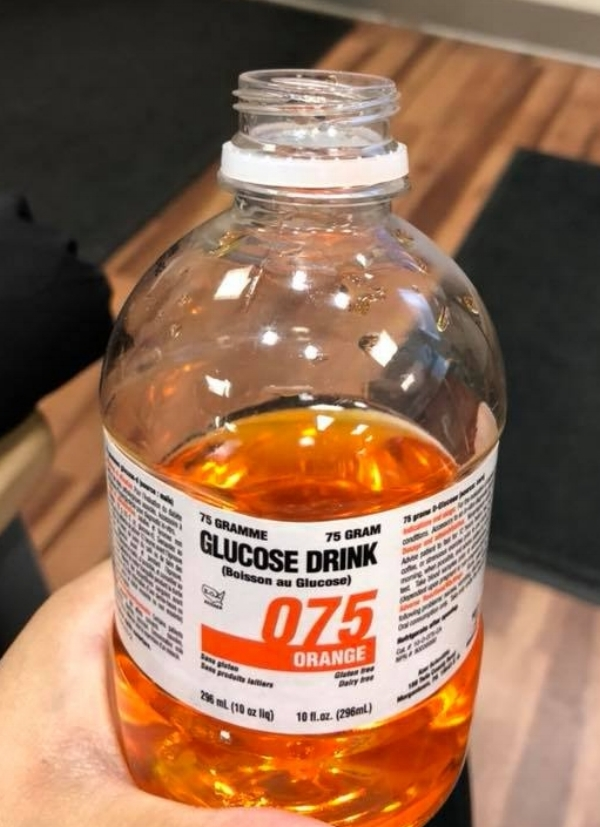Image description: a hand holds a plastic bottle of glucose drink, orange flavour, 75 grams of glucose. photo credit: Sherisa Ritraj