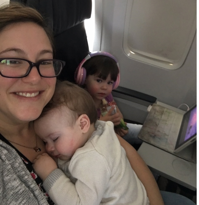 Image Description: Christine travels with her two young children, an infant sleeping on her chest and beside her a toddler watching a tablet with earphones holding a snack.