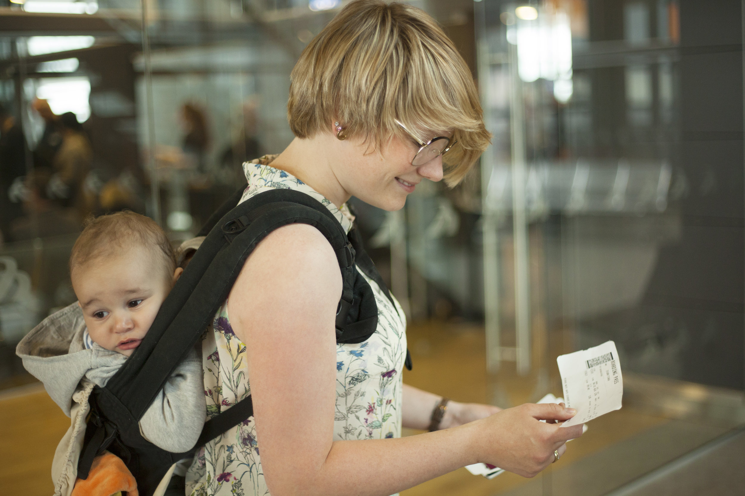 Image description: a baby is back-worn in an infant carrier while the adult looks over a boarding pass