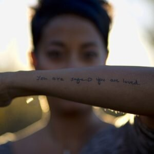 """Image description: aditi holds up her arm in focus of the camera. a tattoo is visible reading, """"you are safe. you are loved""""."""