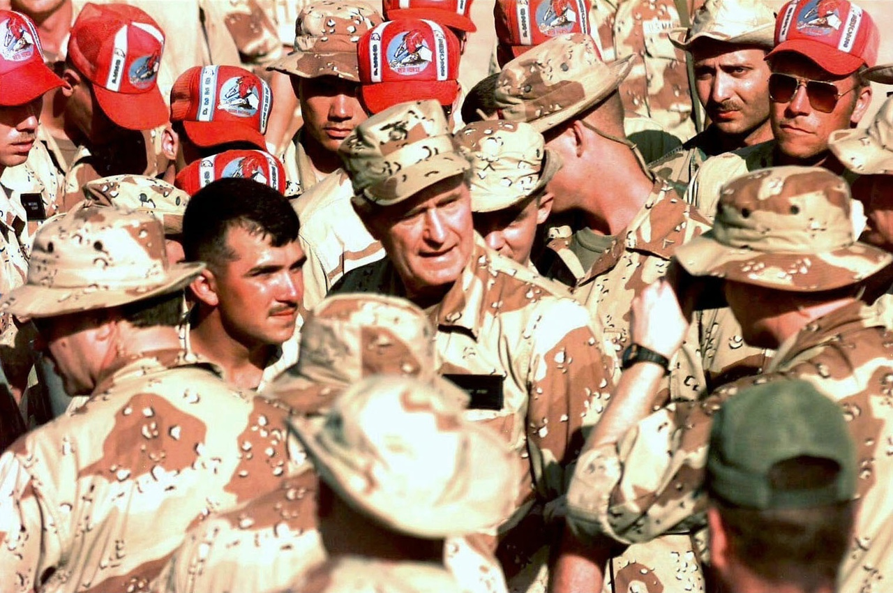 US President George H.W. Bush is surrounded by service members of the US forces assigned to the mission in Mogadishu, Somalia, on January 1, 1993. Those wearing red hats belong to the Air Force Red Horse team from Hurlburt Field, Fla. (US Air Force photo by Tech. Sgt. Dave McLeod)