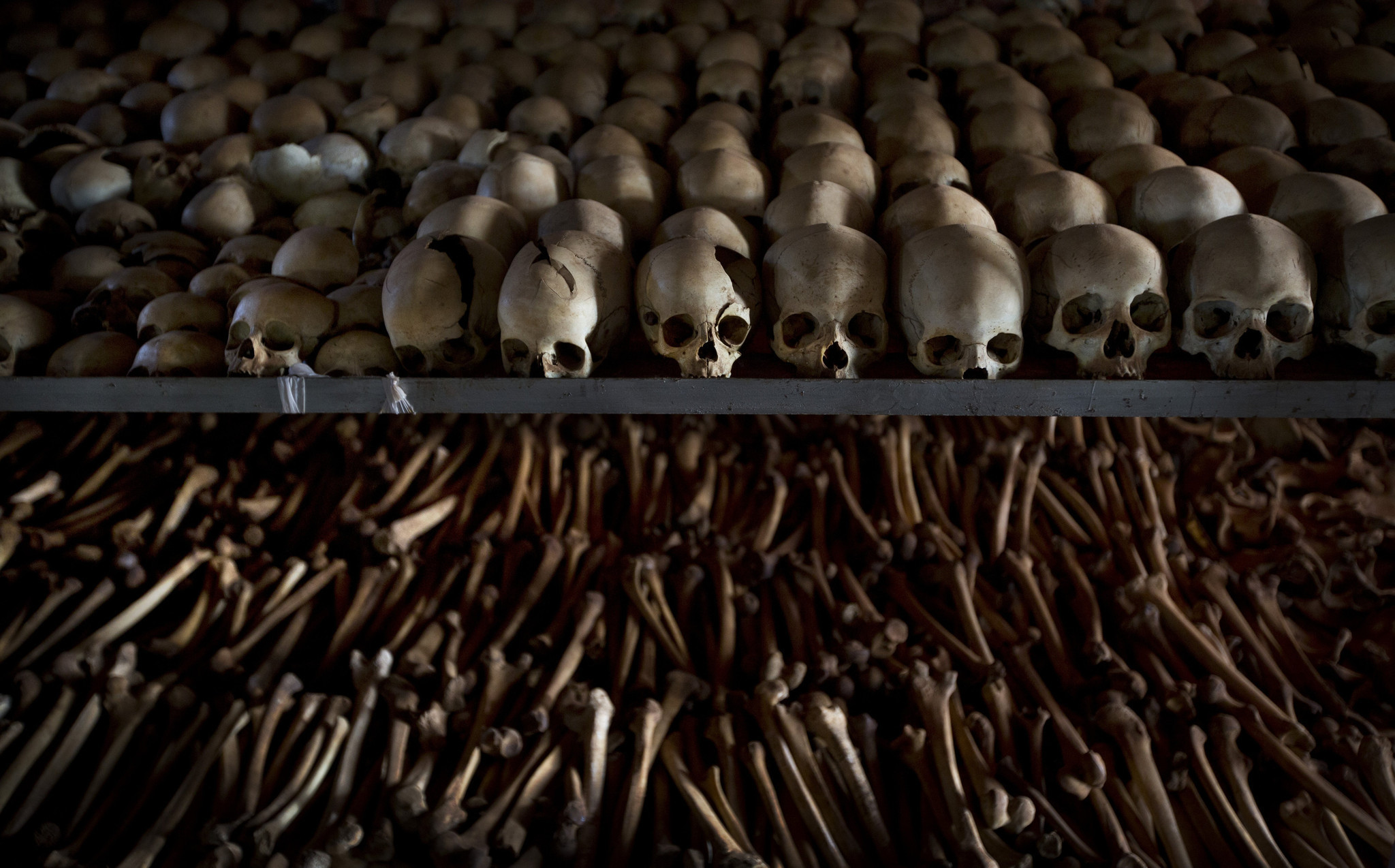 In this April 4, 2014 file photo, the skulls and bones of some of those who were slaughtered as they sought refuge inside the church are laid out as a memorial to the thousands who were killed in and around the Catholic church during the 1994 genocide in Rwanda.  (Ben Curtis / AP)