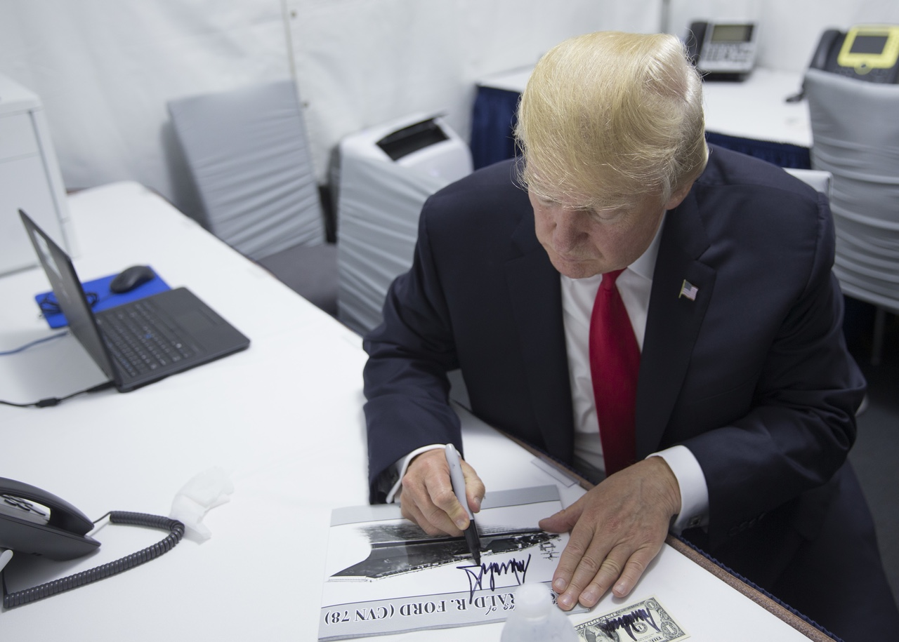 President Donald J. Trump autographs a copy of USS Gerald R. Ford's (CVN 78) commissioning program before making his remarks at the commissioning ceremony at Naval Station Norfolk on July 22, 2017. (U.S. Navy photo by Mass Communication Specialist 3rd Class Matthew R. Fairchild.)