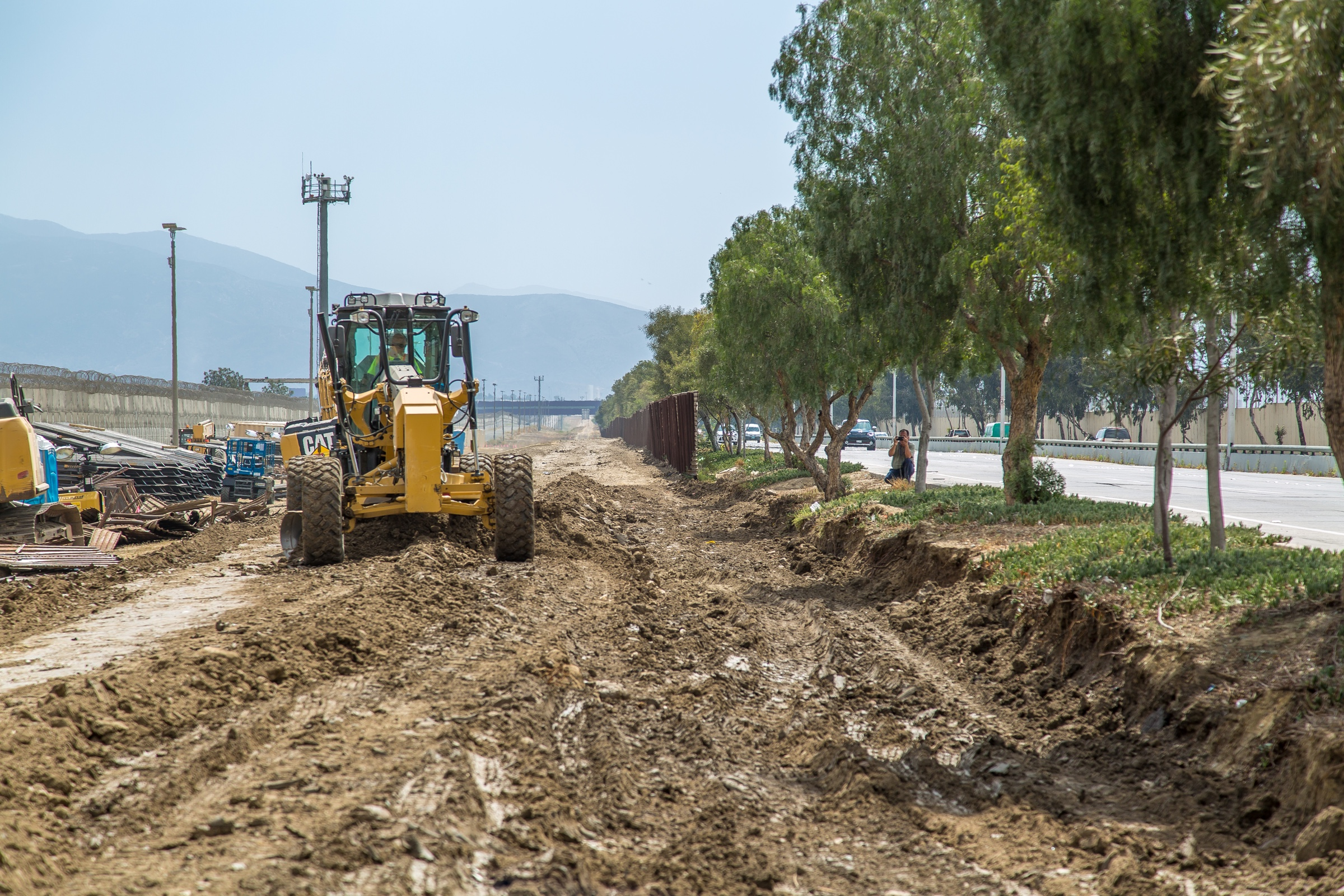 "Caption from CBP: ""Construction workers putting up new wall at the border located at the Chula Vista Area of Responsibility, California, on June 19, 2018. Seen here from the East the ground is being prepared for trenching by construction workers."""