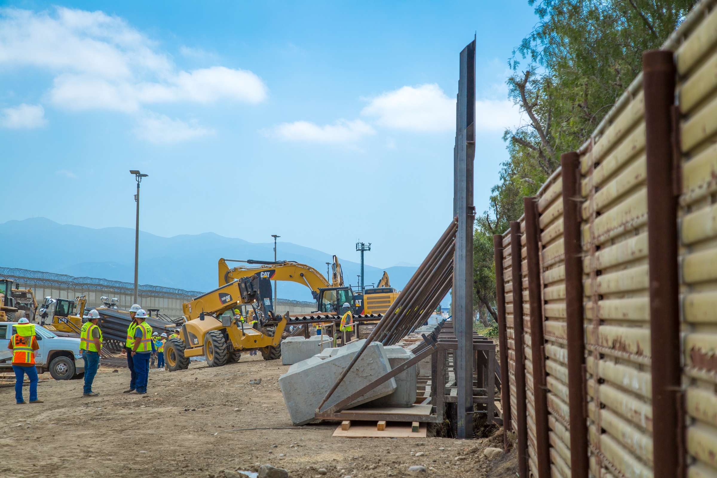 "Caption from CBP: ""Construction workers putting up new wall at the border located at the Chula Vista Area of Responsibility, California, on June 19, 2018. Seen here from the West is the trench with new panels in the background."""