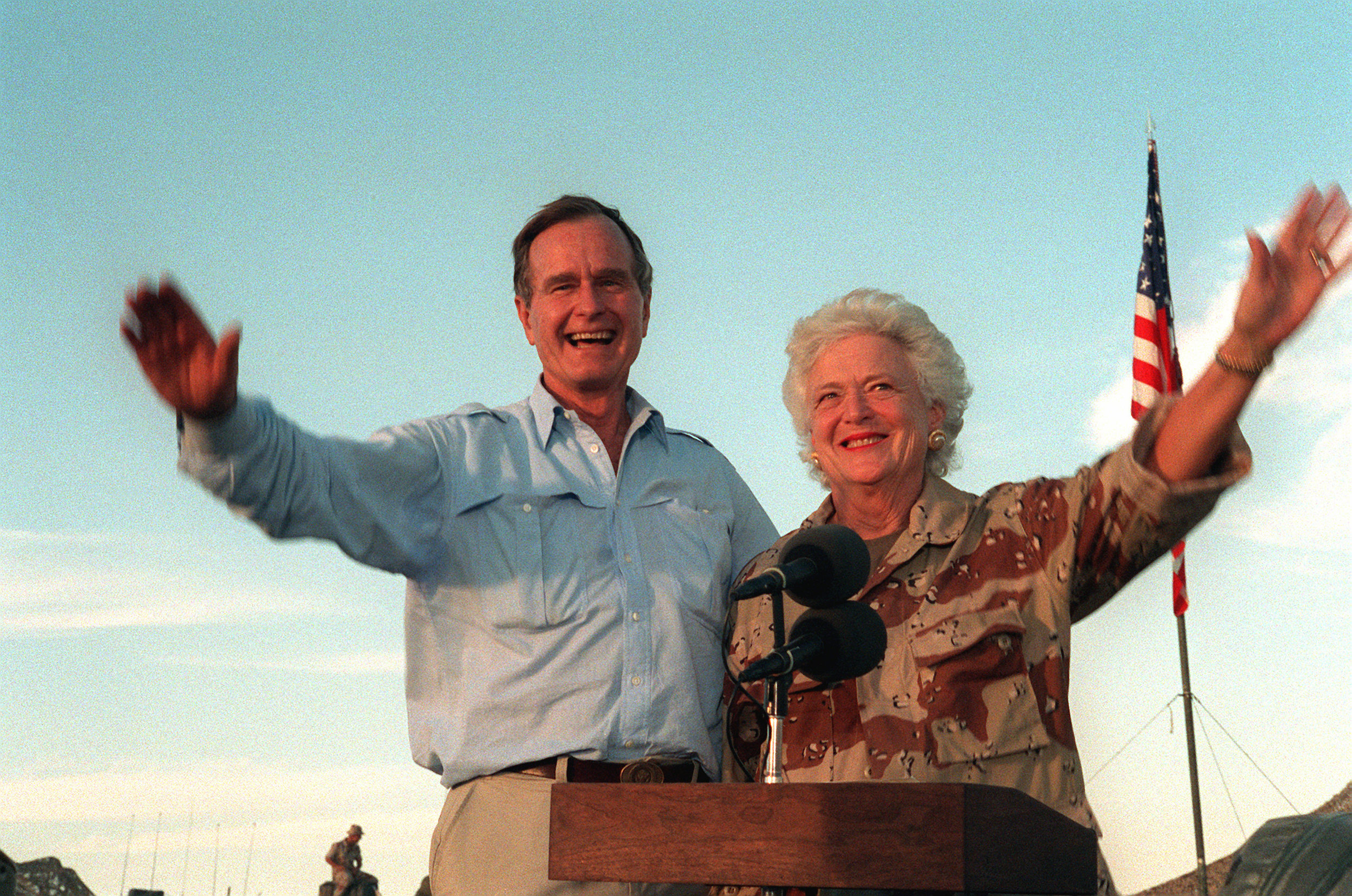 U.S. President George H.W. Bush and first lady Barbara Bush wave as they stand in the back of a vehicle during a visit to a desert encampment in Saudi Arabia, Nov. 22, 1990. The president and his wife are paying Thanksgiving Day visits to U.S. troops who are in Saudi Arabia for Operation Desert Shield. (U.S. Navy photo by CW02 Ed Bailey)