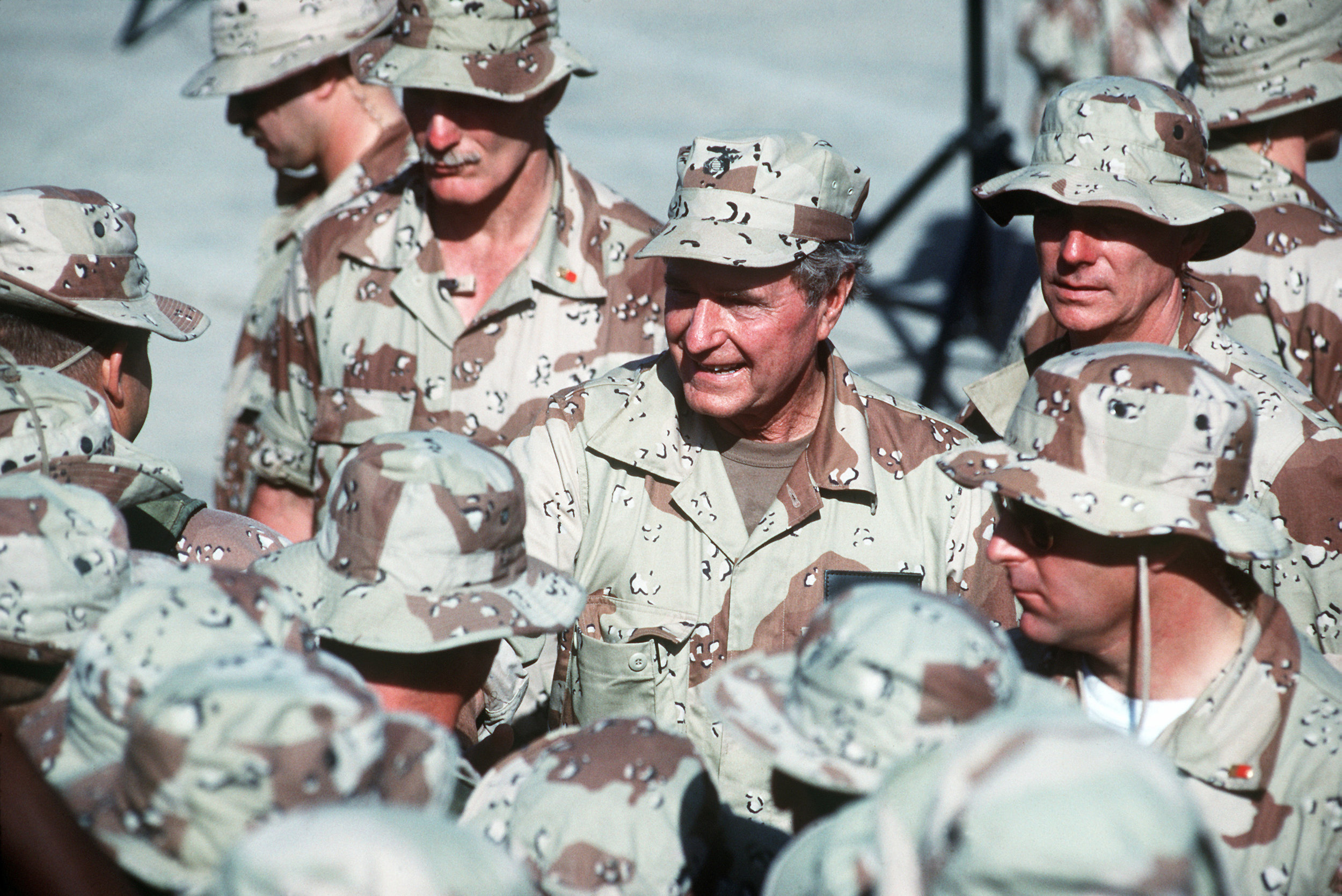 U.S. President George H.W. Bush shakes hands and speaks to individuals as he walks through a crowd of U.S. troops during Operation Restore Hope at the Mogadishu airport in Somalia, Dec. 31, 1992. (U.S. Air Force photo by Master Sgt. Hans H. Deffner)