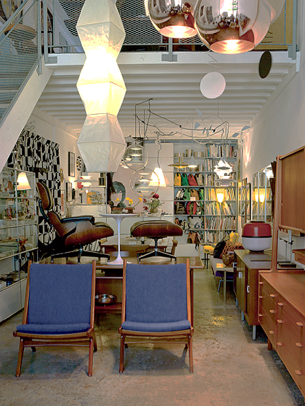 The shop (left and right) is stocked with an array of design books,  pendant lamps, and mid-century teak furniture. The steel candlestick  holder is a Kubus 8, by Mogens Lassen.