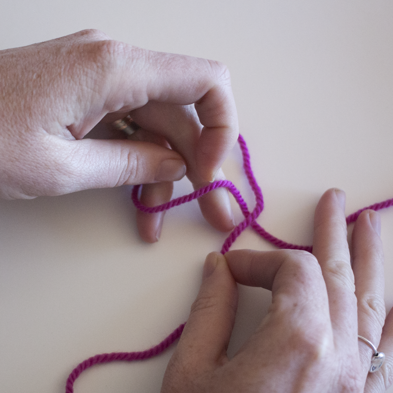 Pull the yarn that crosses over the other under and through the opening.