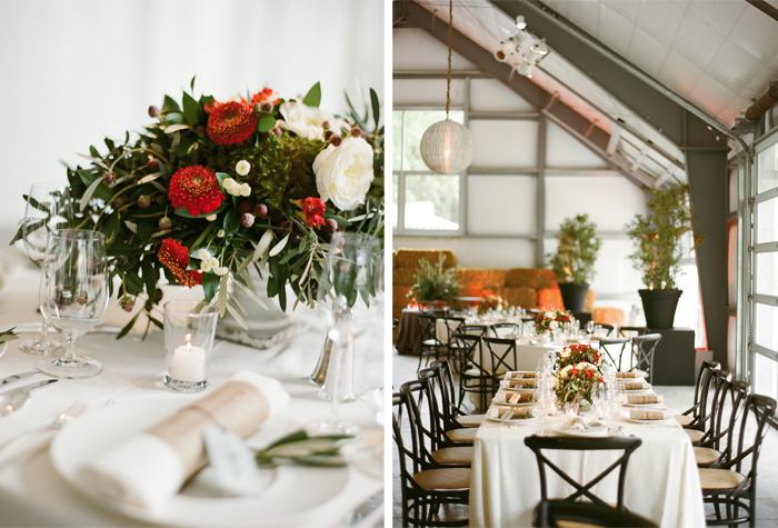 In the center of the tables was an arrangement of red and white flowers, surrounded by dark green and white leaves.