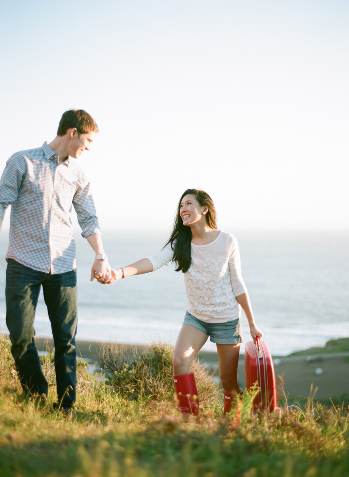 Sylvie-Gil-Engagement-Film-Photography-couple-holding-hands-red-rainboots-hunter-suitcase-vintage.jpg