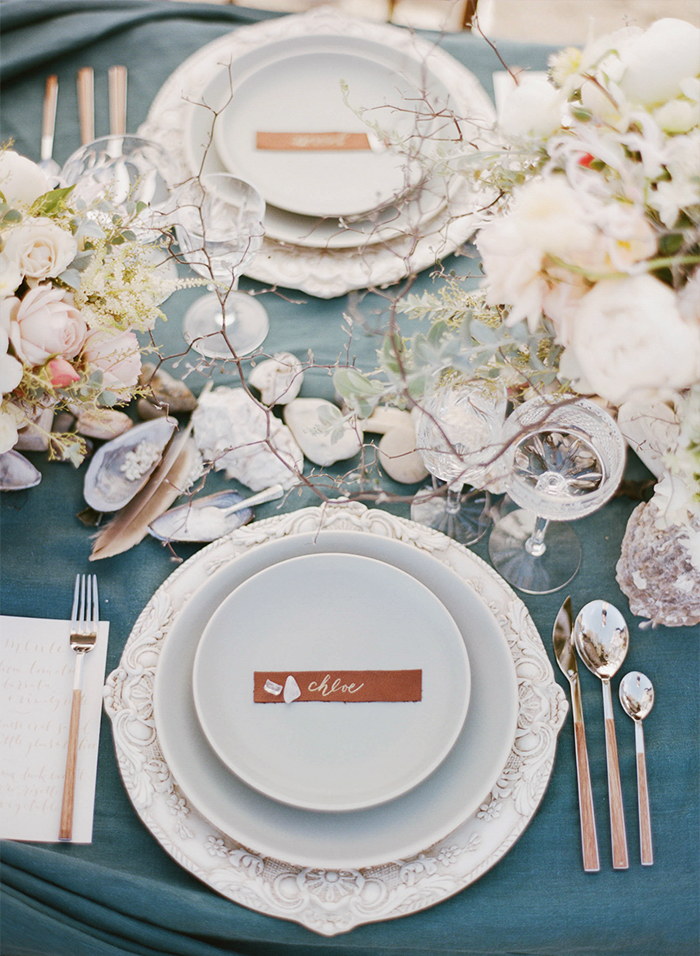Romantic nautical reception table decorated with shells, feathers, and coral; Sylvie Gil Photography