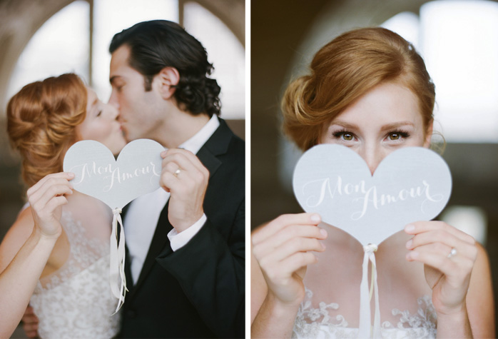 "Bride and groom kiss holding a sign saying ""mon amour"" at their Paris-inspired San Francisco City Hall wedding; Sylvie Gil Photography"