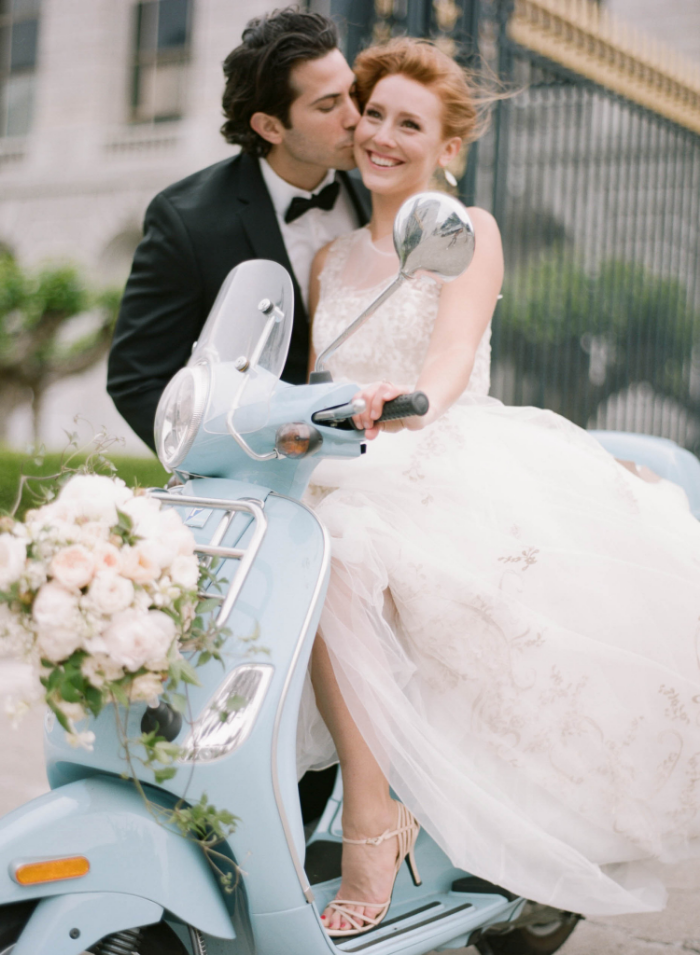 Groom kisses bride on a baby blue Vespa scooter outside San Francisco City Hall wedding; Sylvie Gil Photography