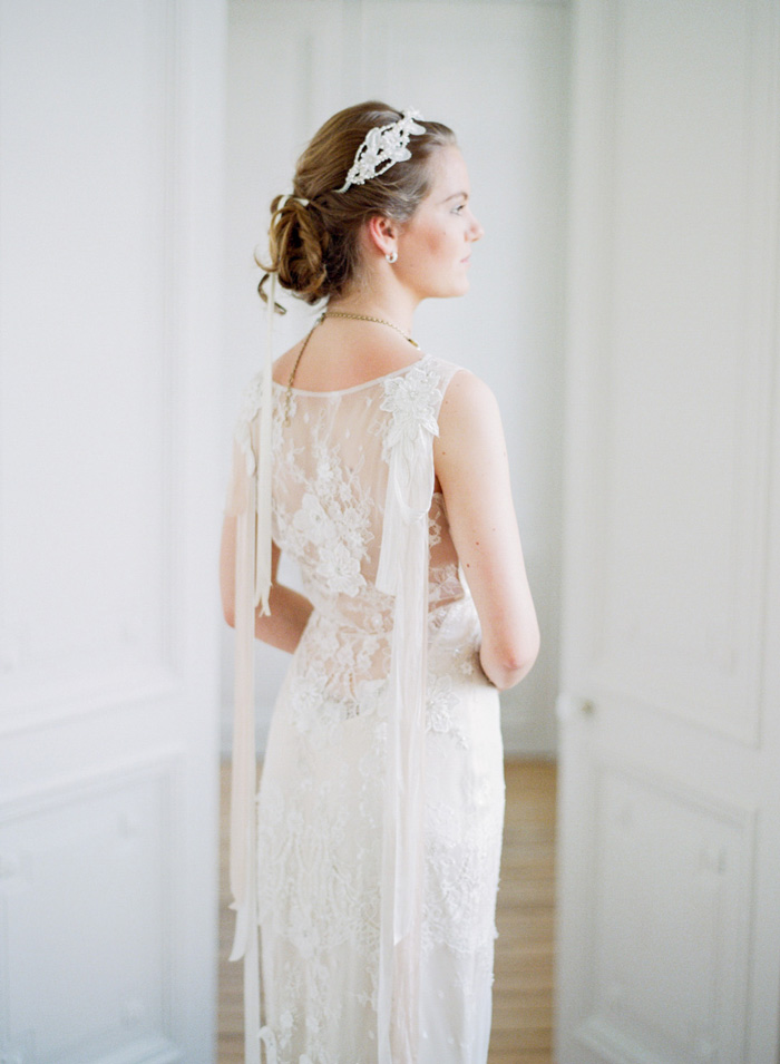 Bride with lace hairpiece stands in Normandy chateau in lace wedding gown; Sylvie Gil Photography