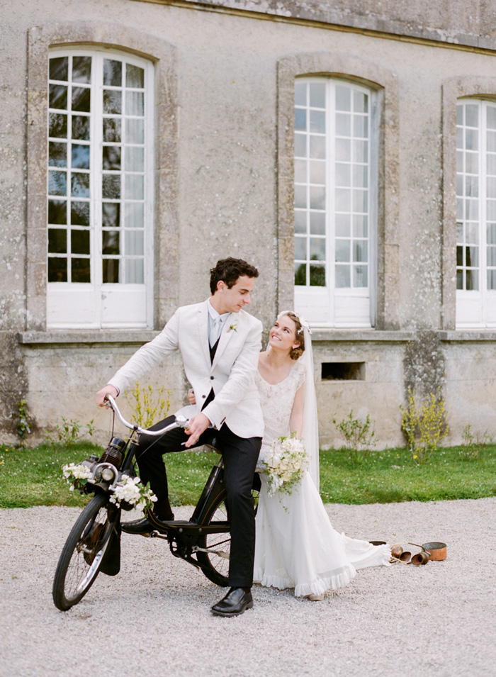 Bride and groom ride away on vintage black Solex bicycle outside Normandy chateau in France; Sylvie Gil Photography