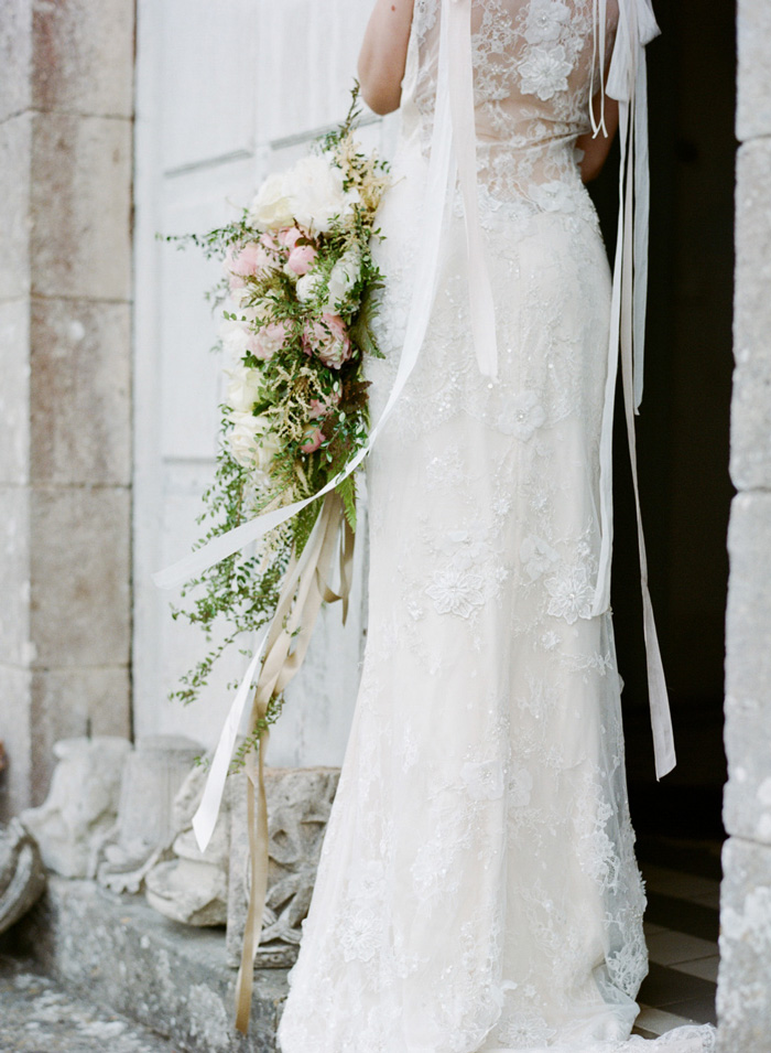 Bride stands in chateau doorway with cascading ribbon and pastel floral bouquet;  Sylvie Gil Photography