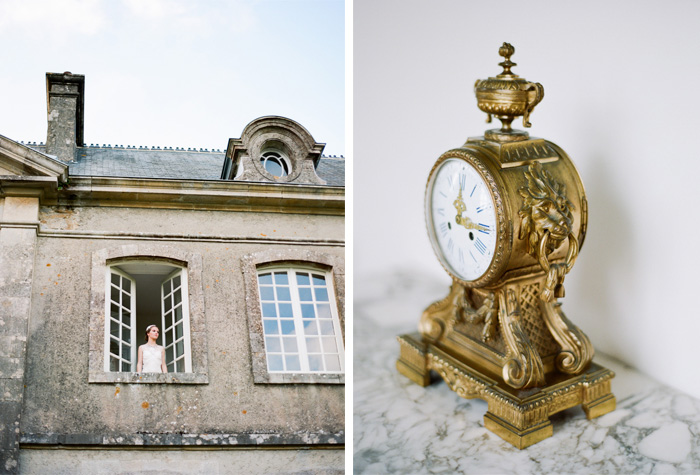 Bride stands at chateau window in Normandy, France, vintage gold clock on marble shelf; Sylvie Gil Photography