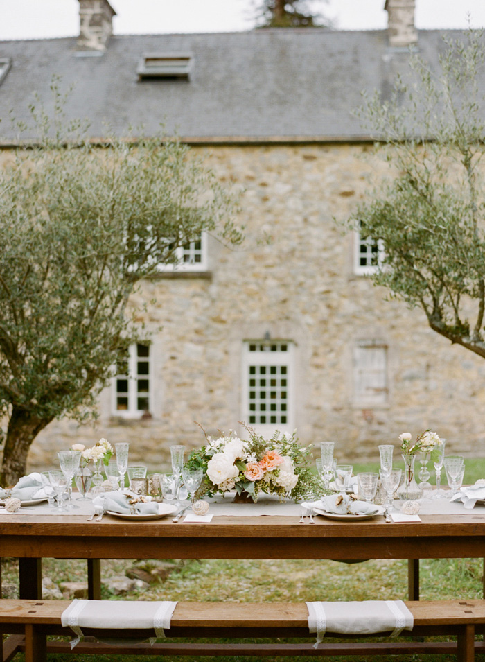 Elegant reception table settings on oak picnic table outside Normandy chateau in France;  Sylvie Gil Photography