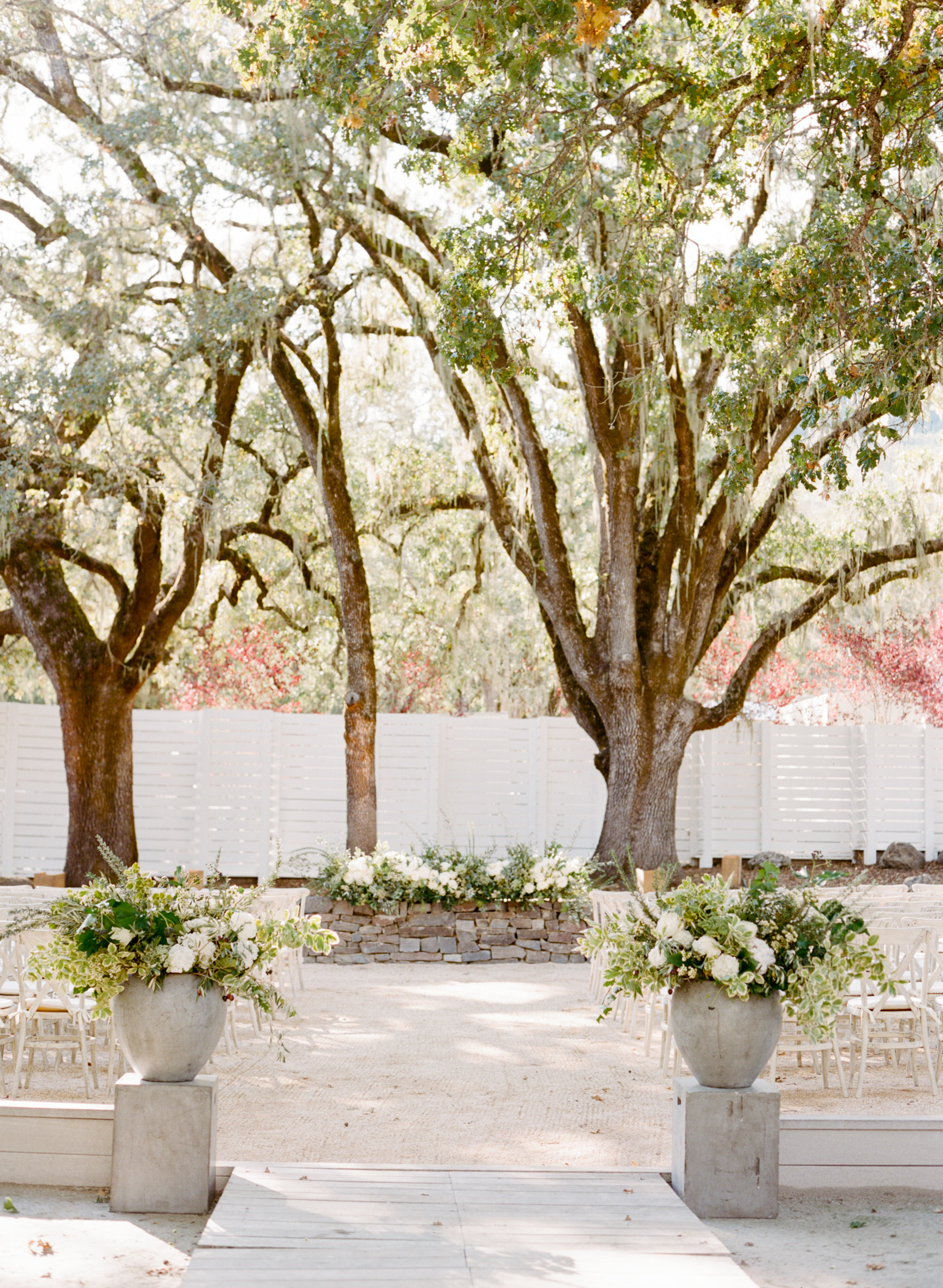 Ceremony aisle entrance with cement floral planters;Sylvie Gil Photography