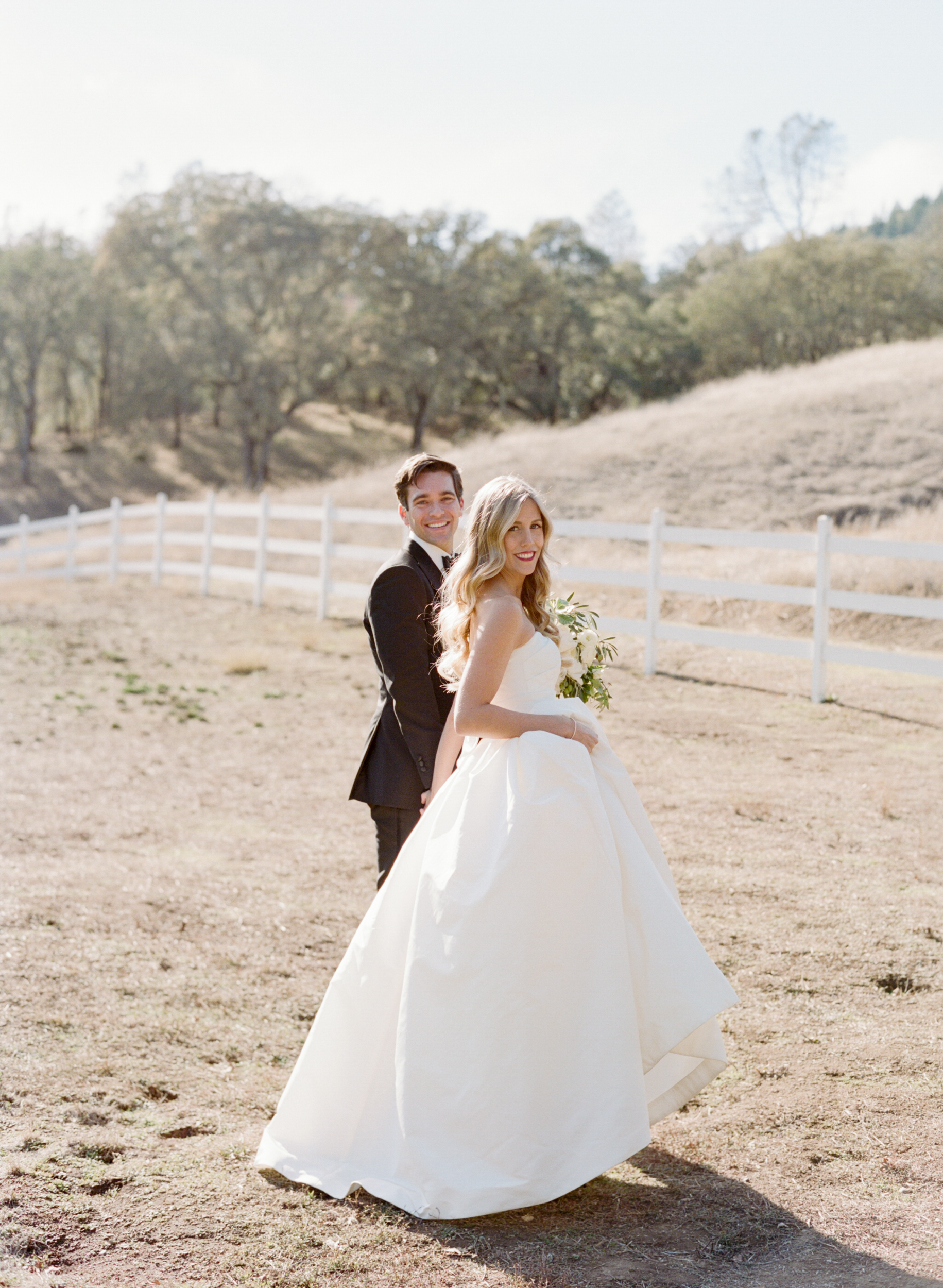 Bride and groom smile, holding hands in a pasture; Sylvie Gil Photography