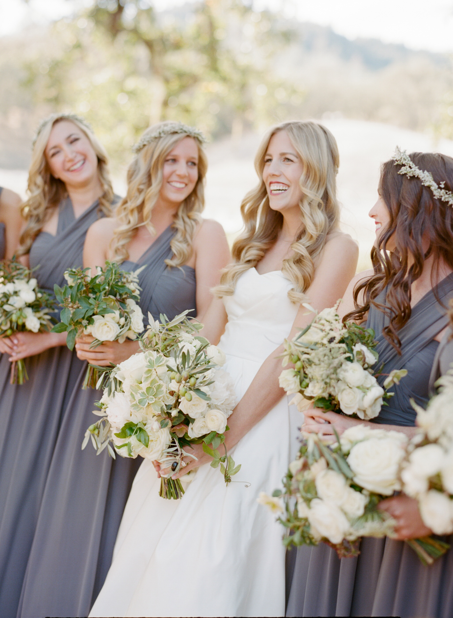 Bride laughs with bridesmaids wearing flower crowns and grey gowns; Sylvie Gil Photography