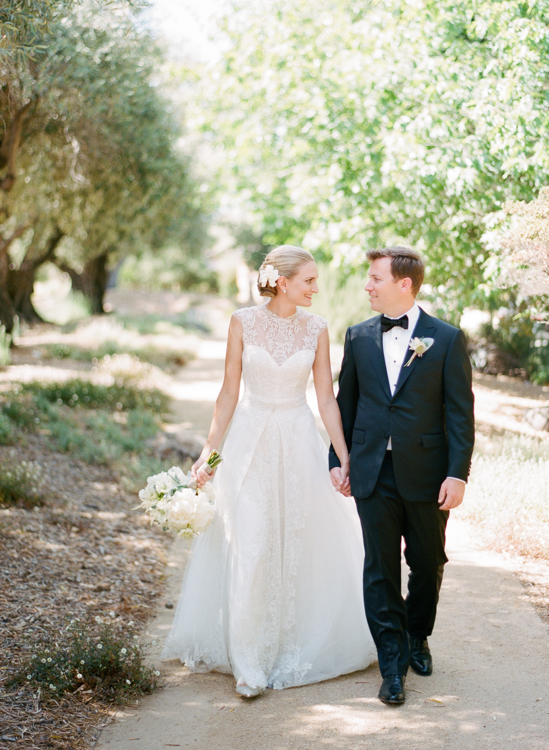 Bride and groom walk hand in hand through an olive grove, the bride wearing a gorgeous Monique Lhuillier gown; photo by Sylvie Gil