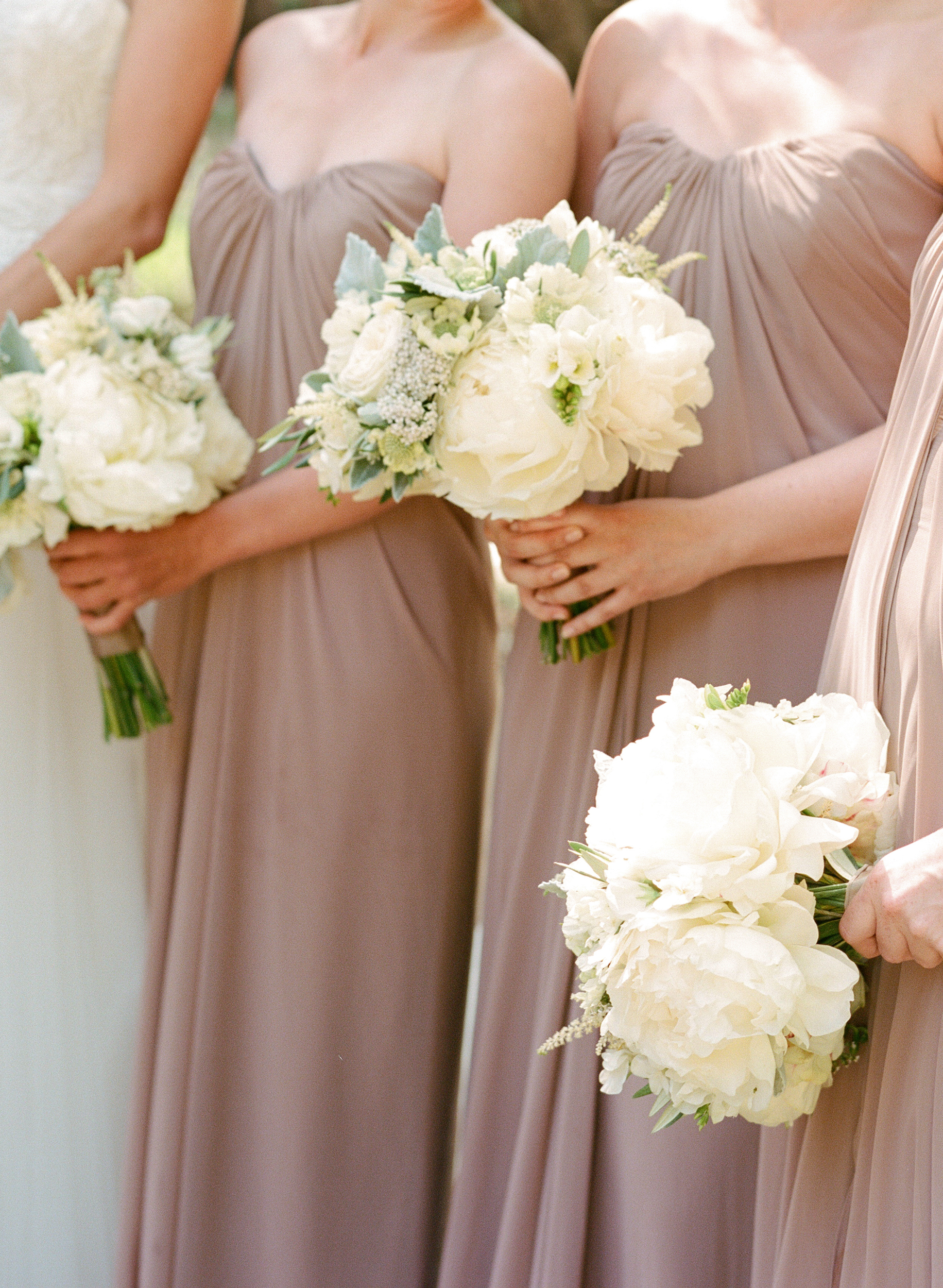 The bridesmaids, dressed in taupe, strapless gowns hold bouquets of roses and peonies matching the bride's; photo by Sylvie Gil