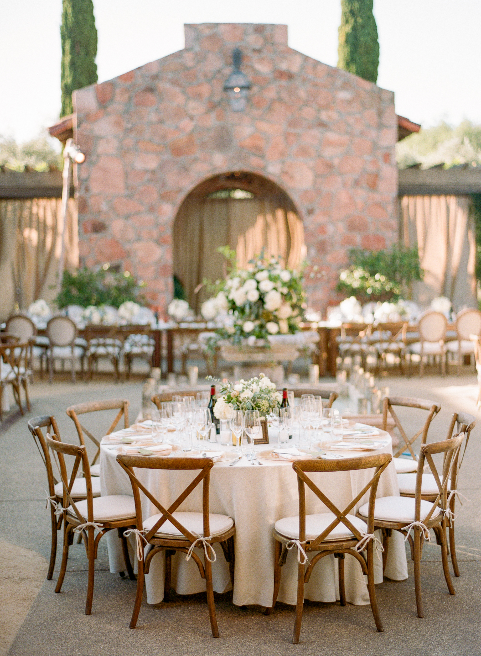 A gorgeous round table elegantly set in a courtyard emanating an Italian dream; photo by Sylvie Gil