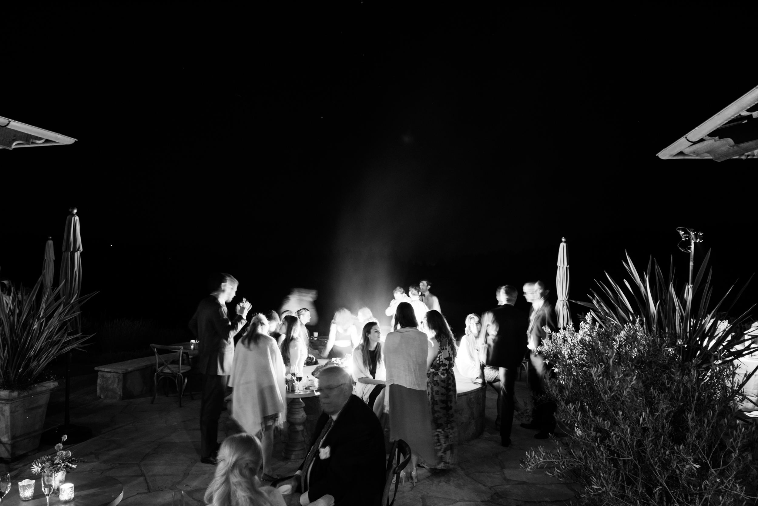 Guests wrapped in shawls stand around a fire pit at the outdoor reception after night has fallen; photo by Sylvie Gil