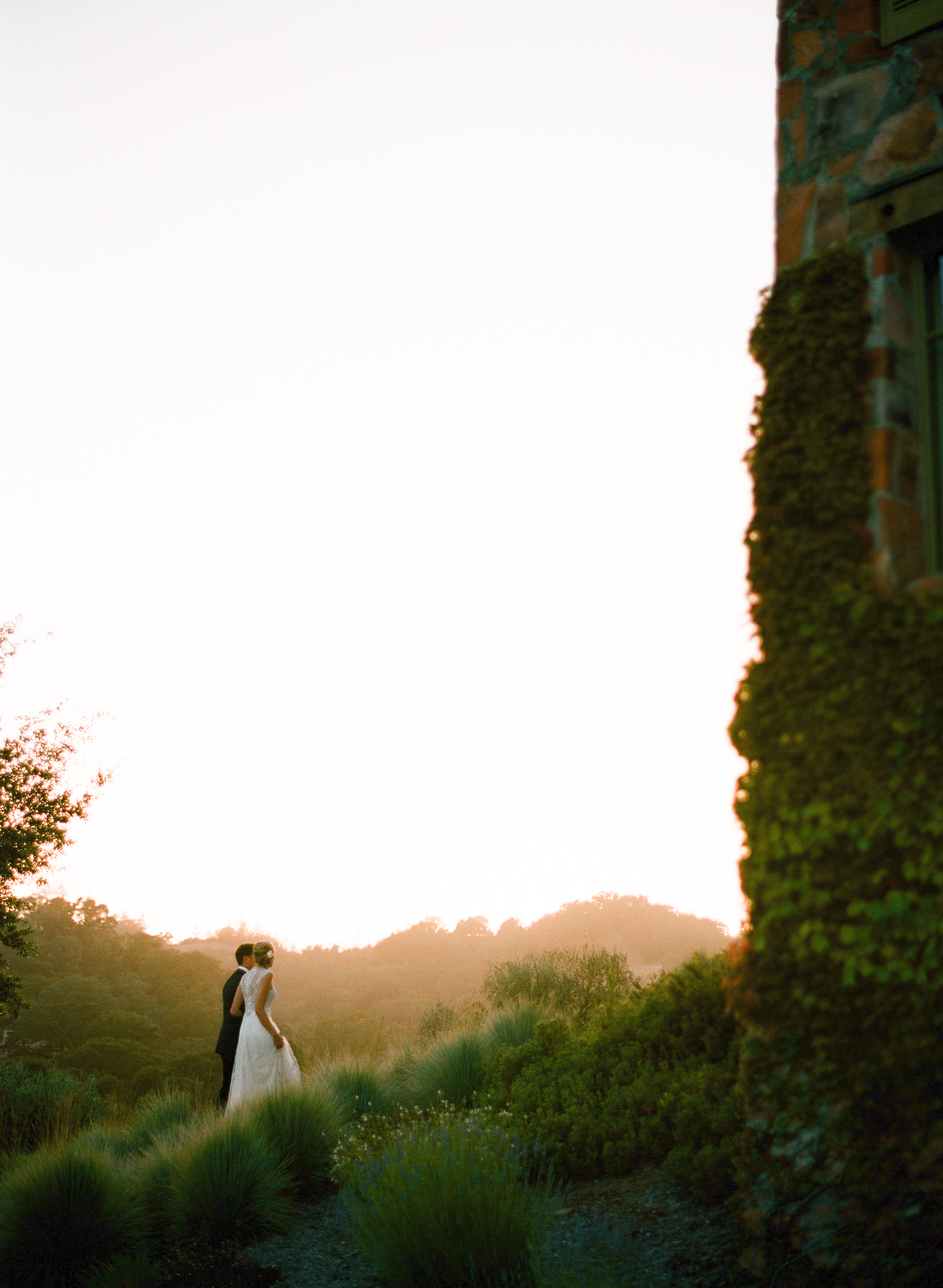 The couple, bathed in the light of sunset, walk off together, viewed from the edge of an old brick wall during a couple shoot with Sylvie Gil