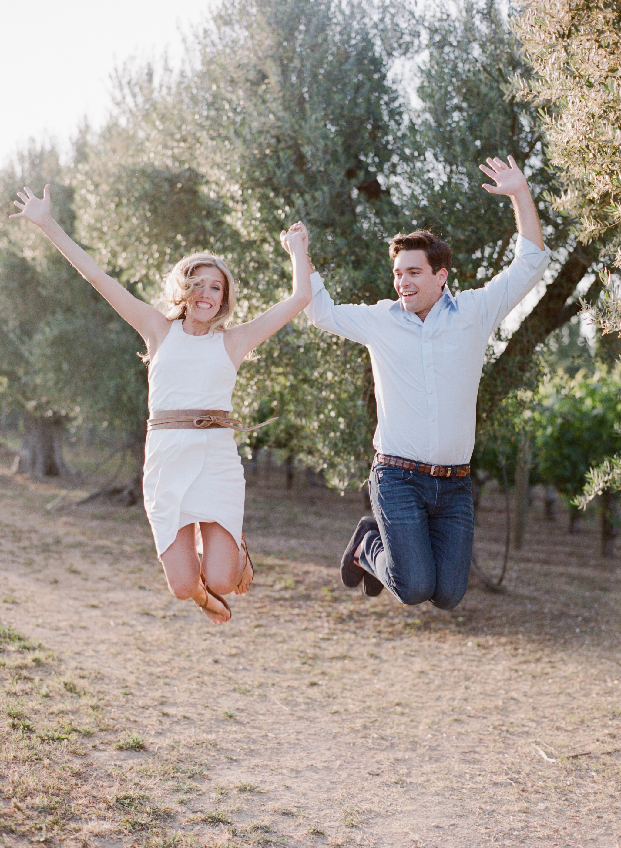 Couple poses for a jump shot holding hands in a Napa Valley vineyard  during an engagement session with Sylvie Gil.