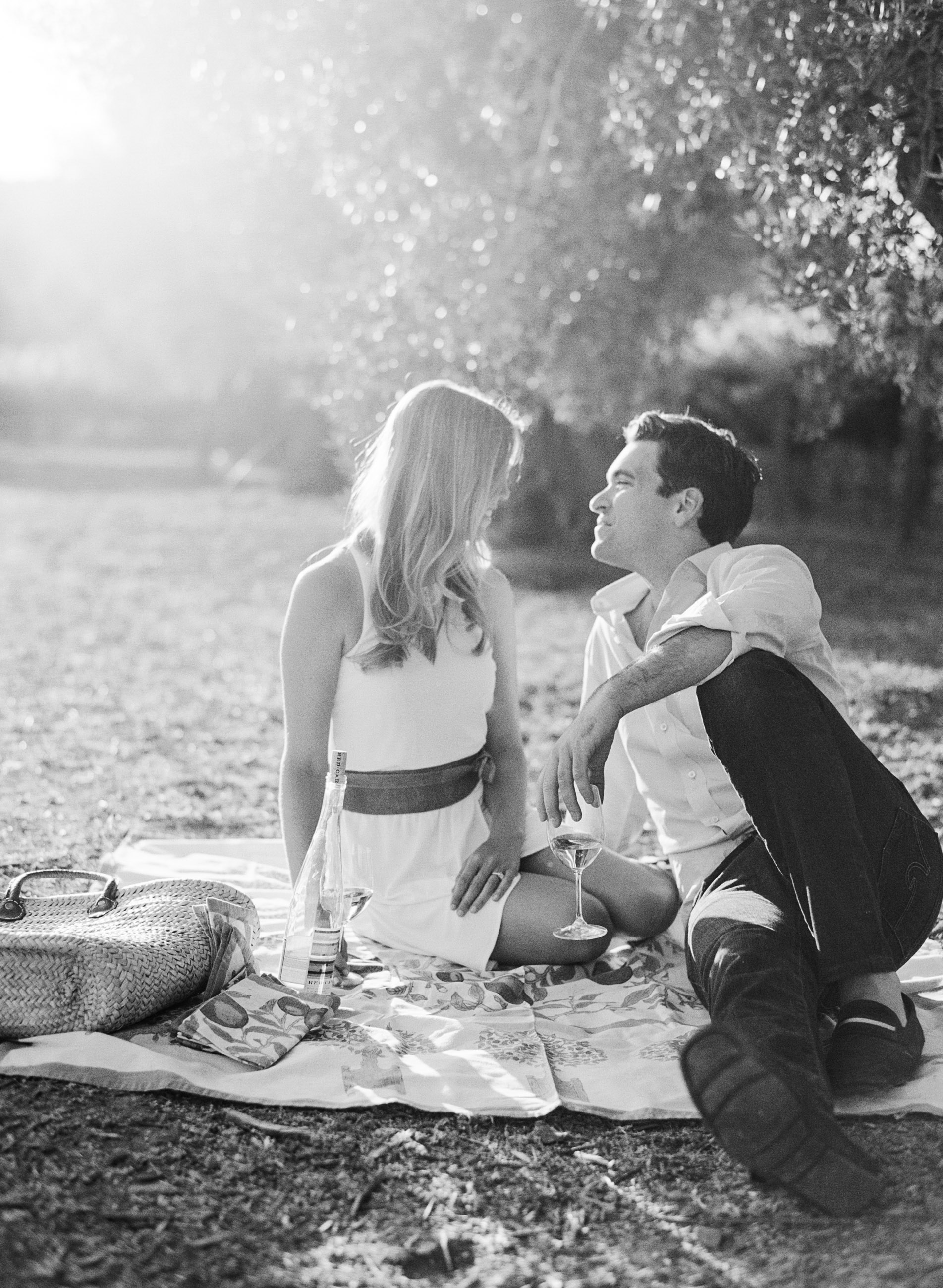 Couple shares a bottle of wine on a picnic blanket in a Napa Valley vineyard  during an engagement session with Sylvie Gil.