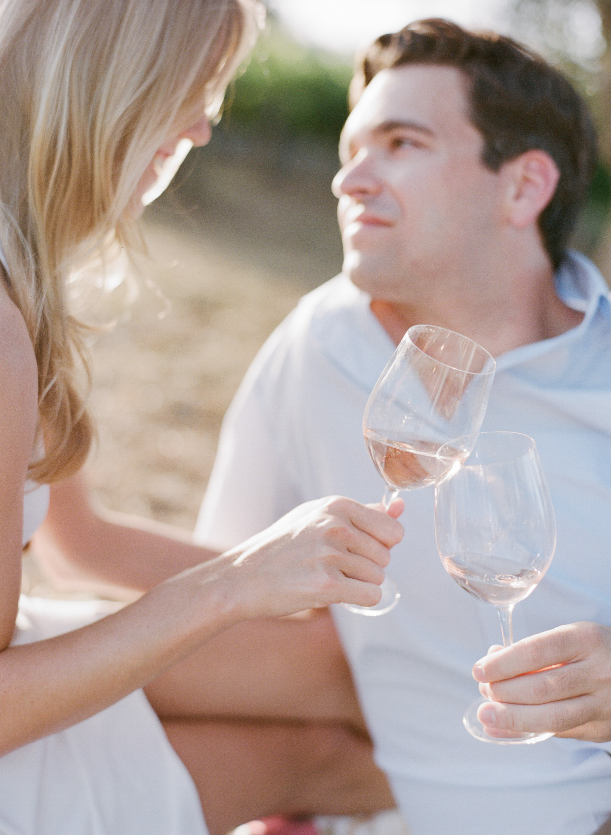A couple toasts their engagement at a Napa Valley winery  during an engagement session with Sylvie Gil.