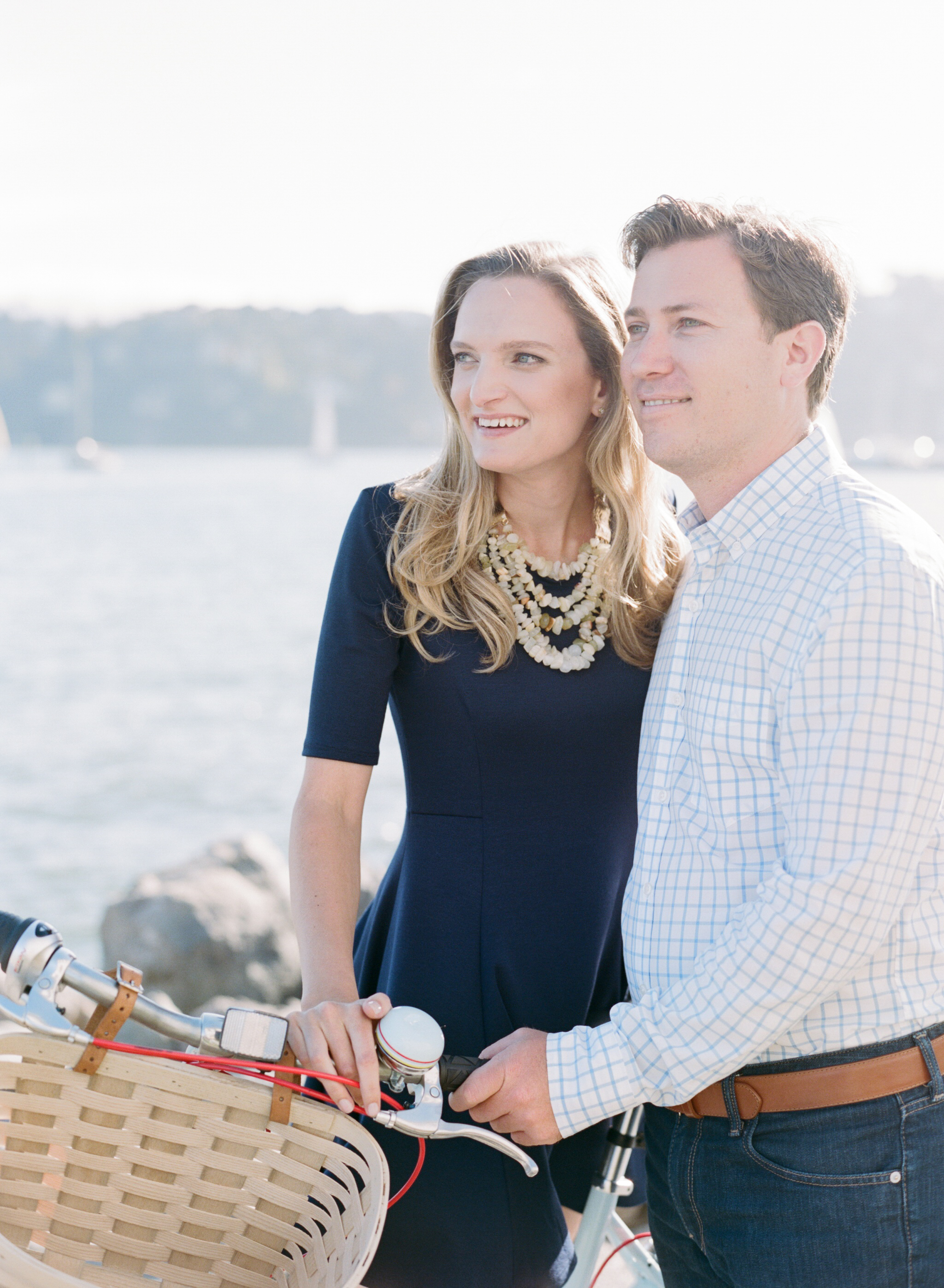 Couple looks out at the Tiburon marina with a bicycle during their engagement session with Sylvie Gil.