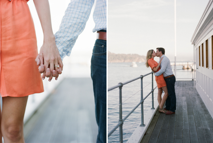Couple holds hands and kisses on the pier in Tiburon during an engagement session with Sylvie Gil.