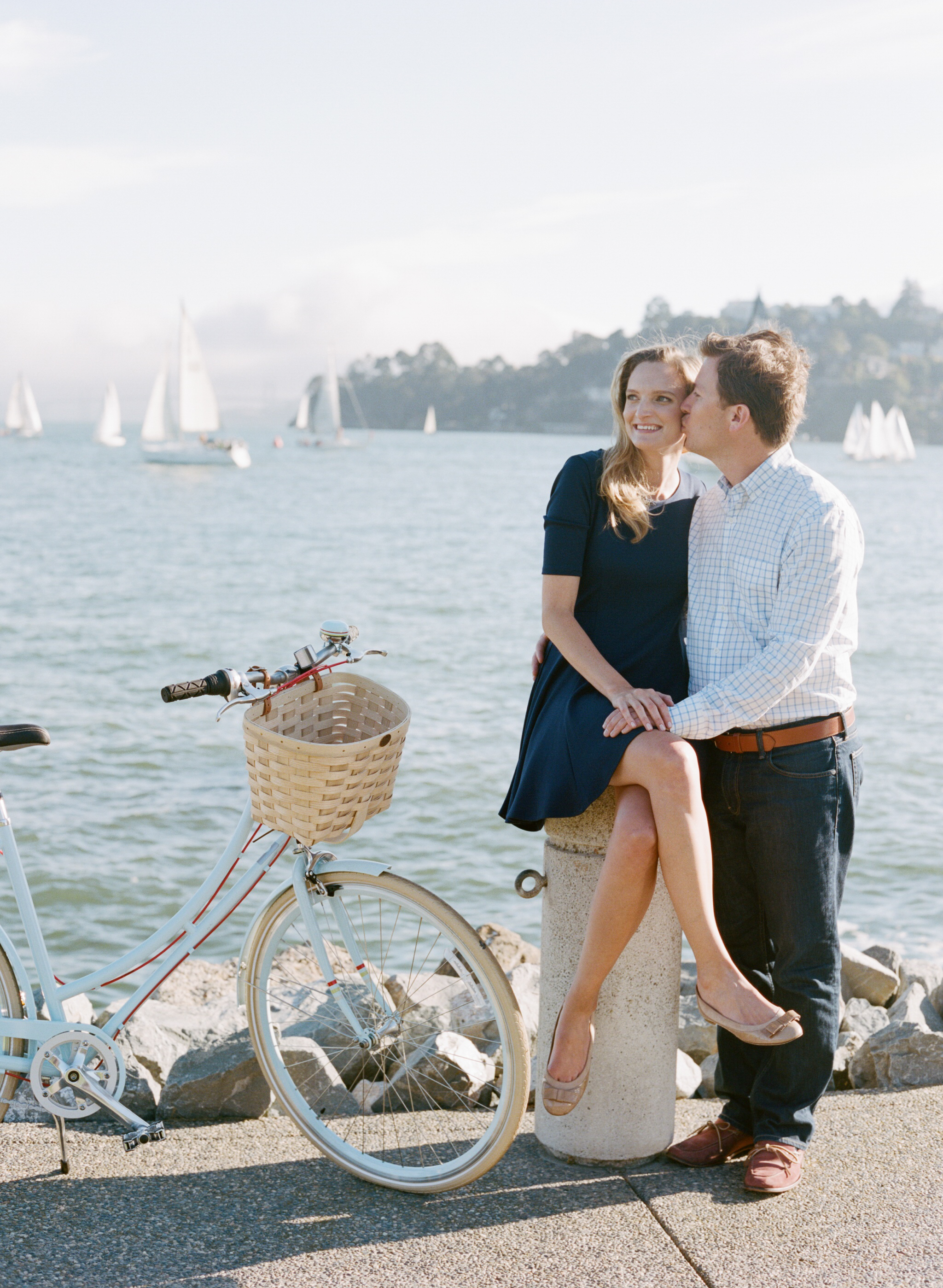 Engaged couple looks out at the Tiburon marina with sailboats behind them during an engagement session with Sylvie Gil.