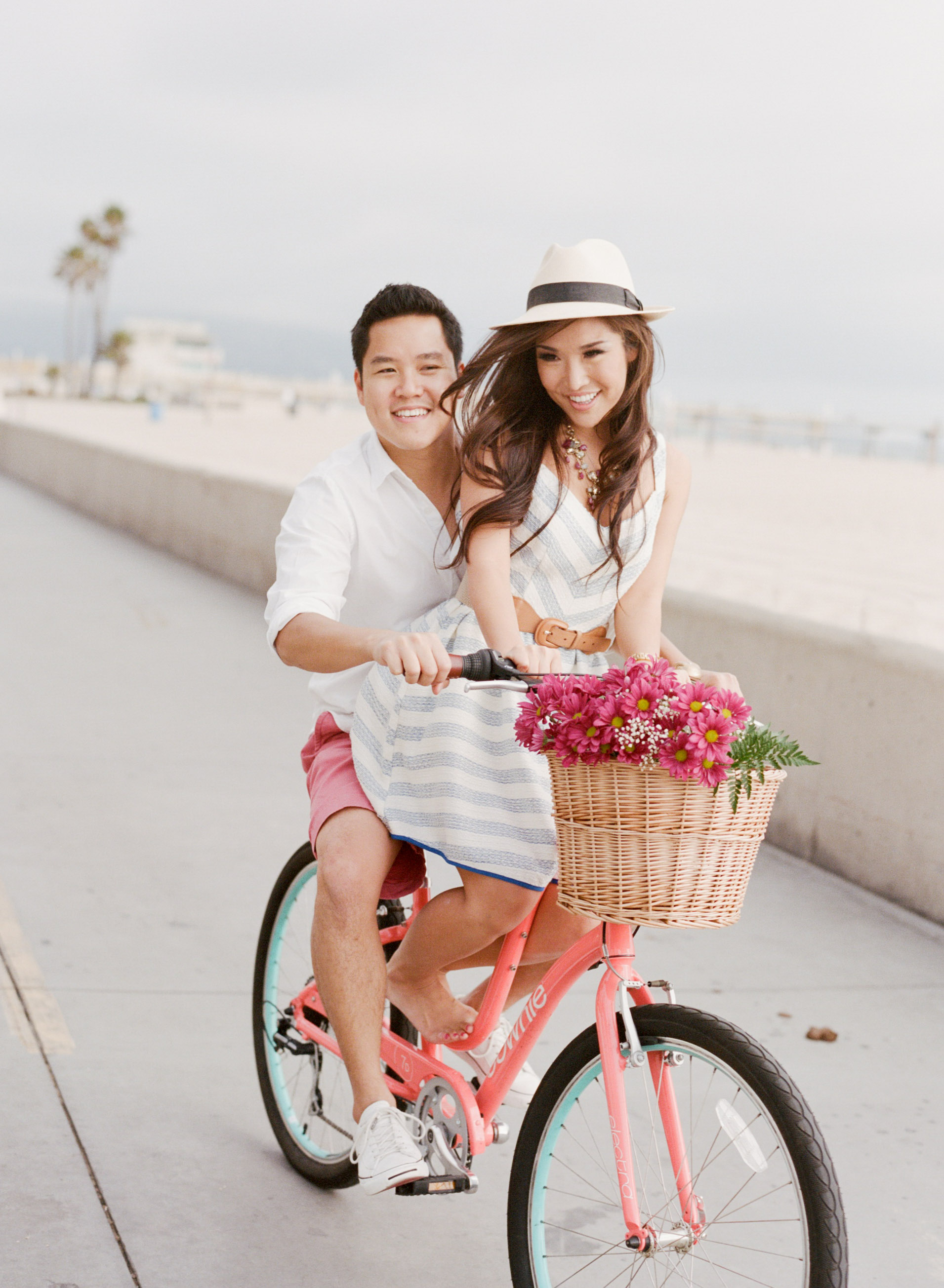 Couple on their pink bicycle with basket of flowers in Hermosa Beach, California during their engagement session with Sylvie Gil.