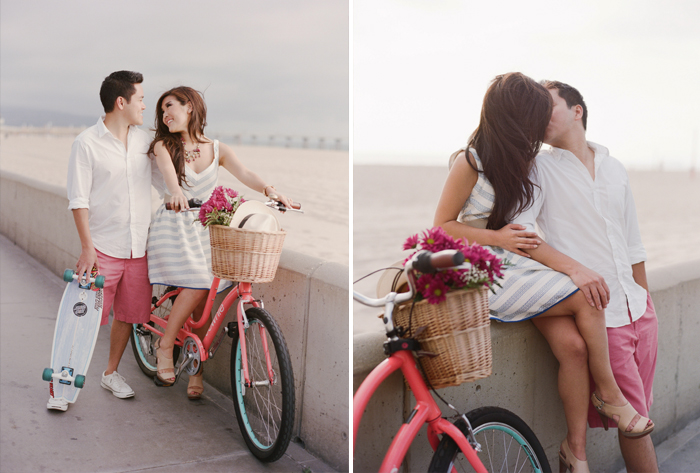 Engaged couple with pink bicycle and skateboard, basket of flowers, during an engagement session in Hermosa Beach, California, with Sylvie Gil.